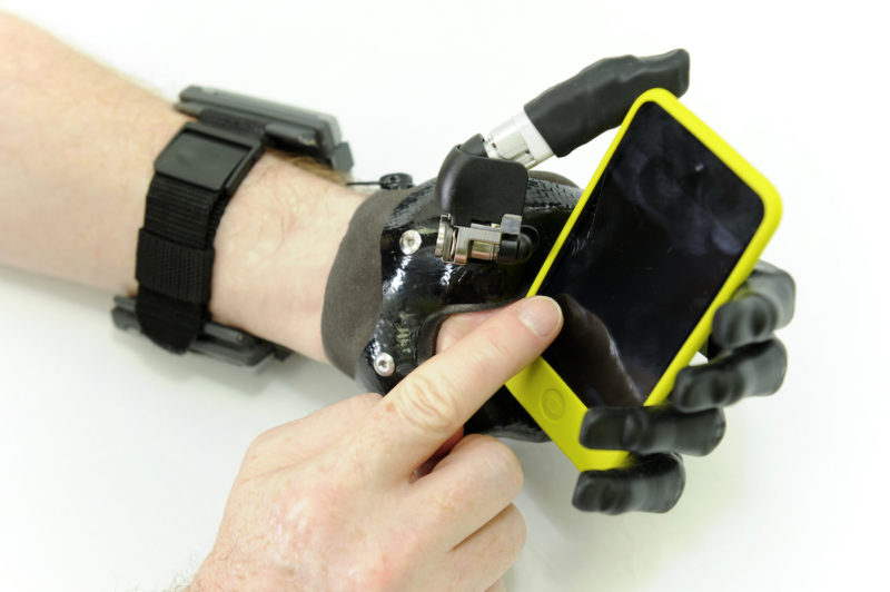 Assistive hand holding a mobile phone