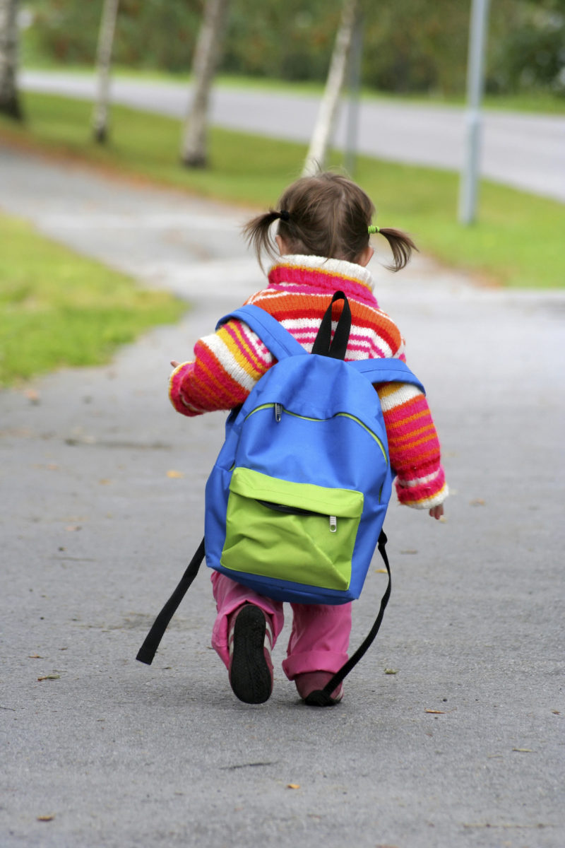 Child wearing a backpack walking to school