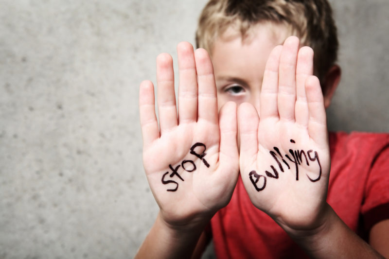 "Child holding hands up with ""stop bulling"" written on palms in black texta"