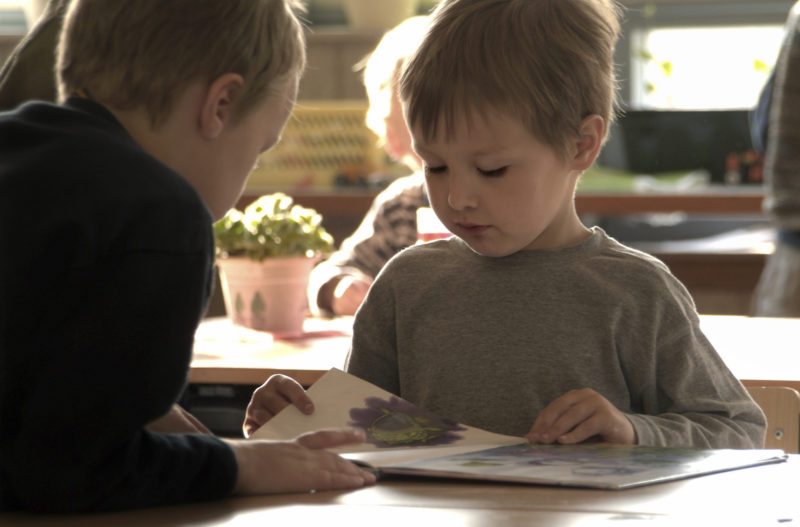 2 children reading a book at a table