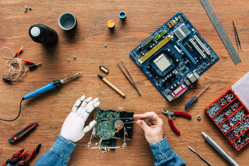 Hands holding tools working on electronic components