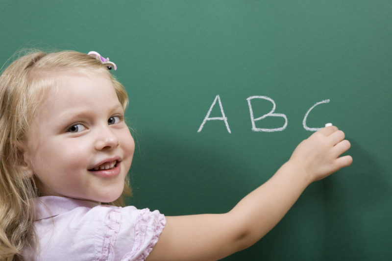 Child writing ABC on a chalkboard