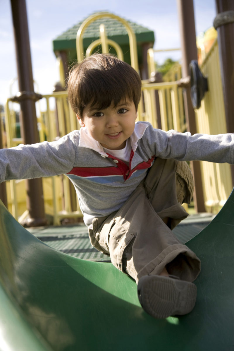 Child smiling and playing in a playground