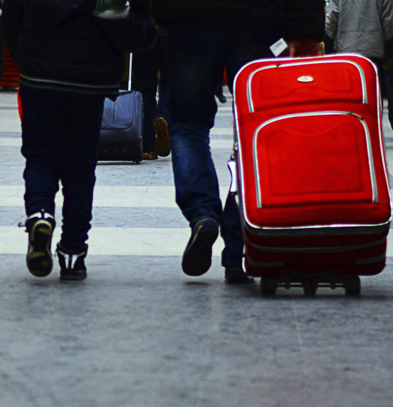 People with suitcases walking in an airport